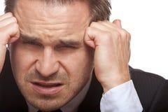 Betonter Geschäftsmann hat falsche Kopfschmerzen im Büro Lizenzfreie Stockfotos
