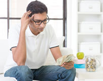 Betonter indischer Kerl, der Geld zählt Lizenzfreie Stockfotografie
