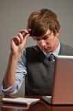 Betonter junger Geschäftsmann auf Laptop Stockbilder