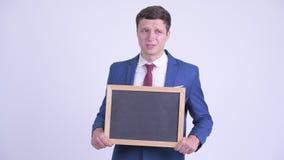 Betonter junger Geschäftsmann, der beim Halten der Tafel traurig schaut stock video footage