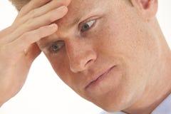 Betonter junger Geschäftsmann mit der Hand auf Stirn Stockfoto