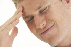 Betonter junger Geschäftsmann mit der Hand auf Stirn Stockfotografie