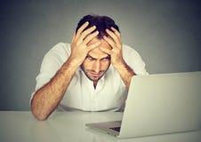 Betonter junger Mann, der an seinem Schreibtisch vor Computer sitzt stockfotos