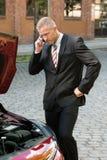 Betonter junger Mann mit seinem Zusammenbruchauto um Mobiltelefon ersuchend stockbilder