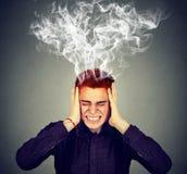 Betonter Mann denkt Kopfschmerzen intensiv, habend stockbilder