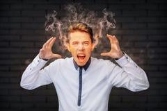 Betonter Mann, der mit dem Rauche herauskommt aus seine Ohren schreit Stockfoto