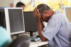 Betonter Mann, der am Schreibtisch im beschäftigten kreativen Büro arbeitet Stockbilder