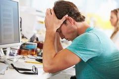 Betonter Mann, der am Schreibtisch im beschäftigten kreativen Büro arbeitet