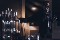 Betonter Mann von mittlerem Alter in einer Klage sprechend auf dem Telefon und dem Griff Stockfotografie