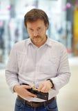 Betonter Mittelaltermann, der Geldbeutel mit russischem Papiergeld hält Stockfotografie