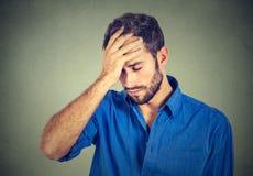 Betonter trauriger junger Mann, der unten auf grauem Wandhintergrund schaut Lizenzfreies Stockfoto