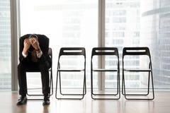 Betonter umgekippter Geschäftsmann, der auf Stuhl, empfangene schlechte Nachrichten sitzt Lizenzfreies Stockfoto
