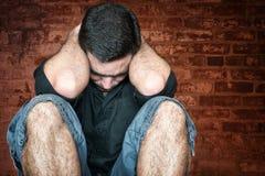 Betonter und trauriger junger Mann, der auf dem Boden sitzt Lizenzfreie Stockfotos