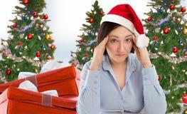Betontes Fraueneinkaufen für die Geschenke, welche die Weihnachtsgeschenke tragen roten Sankt-Hut schaut verärgert und beunruhigt Stockbild