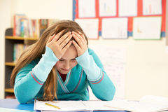 Betontes Schulmädchen, das im Klassenzimmer studiert Stockbilder