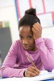 Betontes Schulmädchen, das im Klassenzimmer studiert Lizenzfreie Stockbilder