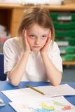 Betontes Schulmädchen, das im Klassenzimmer studiert Stockfotos