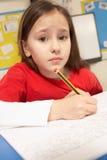 Betontes Schulmädchen, das im Klassenzimmer studiert Stockfoto