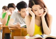 Betontes Schulmädchen, das im Klassenzimmer studiert Lizenzfreies Stockfoto