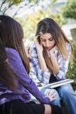 Betontes trauriges junges Mischrasse-Mädchen, das vom Freund getröstet wird Lizenzfreie Stockfotos