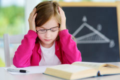 Betontes und müdes Schulmädchen, das mit einem Stapel von Büchern auf ihrem Schreibtisch studiert Lizenzfreies Stockfoto