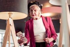 Betoverend elegante hogere dame die verkoopteken ter beschikking bekijken royalty-vrije stock foto's
