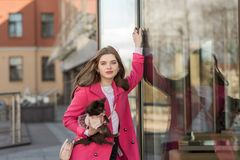 Betoverend meisje in een roze laag met een kleine hond royalty-vrije stock foto