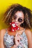 Betoverend mooie afro Amerikaans meisje die zonnebril dragen die lolly houden stock fotografie