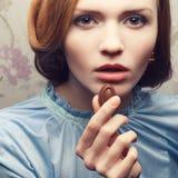 Betoverend roodharig (gember) meisje die in blauwe kleding suikergoed eten stock afbeelding