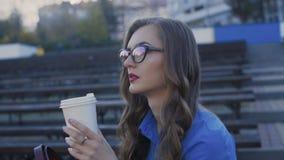 Betoverende damerust op een bank en van de dranken smakelijke straat koffie 4K stock video