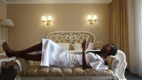 Betoverende en sexy Afrikaanse Amerikaanse dame in witte cocktailkleding die haar tabletcomputer met behulp van terwijl binnen he stock footage
