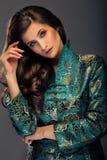Betoverende jonge vrouw die in groen Japans stijljasje streptokok kijken stock foto's