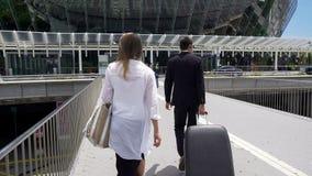 Betoverende wijfje en lijfwacht die met haar bagage bij luchthaven, toerisme lopen stock foto's