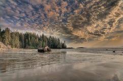 Beträchtlicher Strand mit erstaunlichen Wolken und großem Felsen Stockfoto