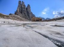 Beträffande Alberto bergkoja och Torri del Vajolet berg med en frostsjö i en solig dag, Dolomites, Italien Royaltyfria Bilder
