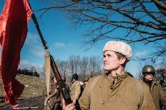 Beträffande-enactor klätt som rysk sovjetisk infanterisoldatOf World War II den hållande röda flaggan Royaltyfri Bild