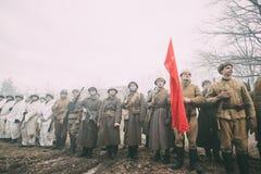 Beträffande-enactors klätt som ryska sovjetiska infanterisoldater av världskrig II som står i rad Arkivfoton
