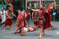 Beträffande gataaktörer - anta korsfästelsen royaltyfria bilder