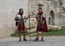 Beträffandesom kläs som Roman Legionnaires, väntar för att posera med turister på portarna till den Diocletian slotten arkivfoton
