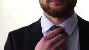 Betrüger in einem Hemd mit einer Bindung, die auf eine Jacke sich setzt und Bindungsnahaufnahme justiert stock video