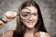 Betrachten der Kamera durch Vergrößerungsglas lizenzfreies stockfoto