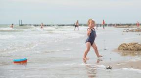 Betrachten der Rückseite eines Babys auf dem Strand mit einem Bootsspielzeug Lizenzfreie Stockfotografie