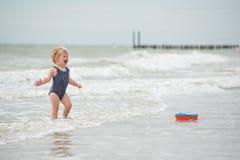 Betrachten der Rückseite eines Babys auf dem Strand mit einem Bootsspielzeug Lizenzfreie Stockfotos