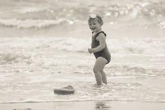 Betrachten der Rückseite eines Babys auf dem Strand mit einem Bootsspielzeug Stockfotografie
