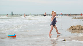 Betrachten der Rückseite eines Babys auf dem Strand mit einem Bootsspielzeug Stockbilder