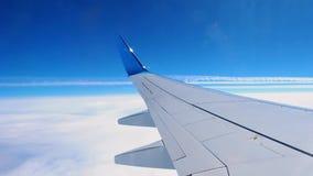 Betrachten durch die Belichtungseinheit des Fliegenflugzeugs Sonnenuntergang Ansicht zum Flügel, zum Himmel und zu den weißen Wol stock footage