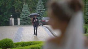 Betrachten Sie über der Schulter der eleganten Braut dem Bräutigam, der unter Regenschirm im Regen geht stock video footage