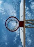 Betrachten Sie den Himmel durch einen Basketballkorb Stockfotos