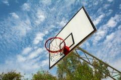 Betrachten Sie den Himmel durch einen Basketballkorb Stockbilder