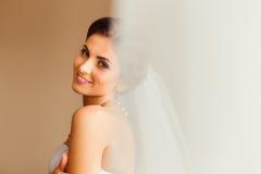 Betrachten Sie durch den Vorhang Brunettebraut mit tiefen blauen Augen lizenzfreie stockfotos